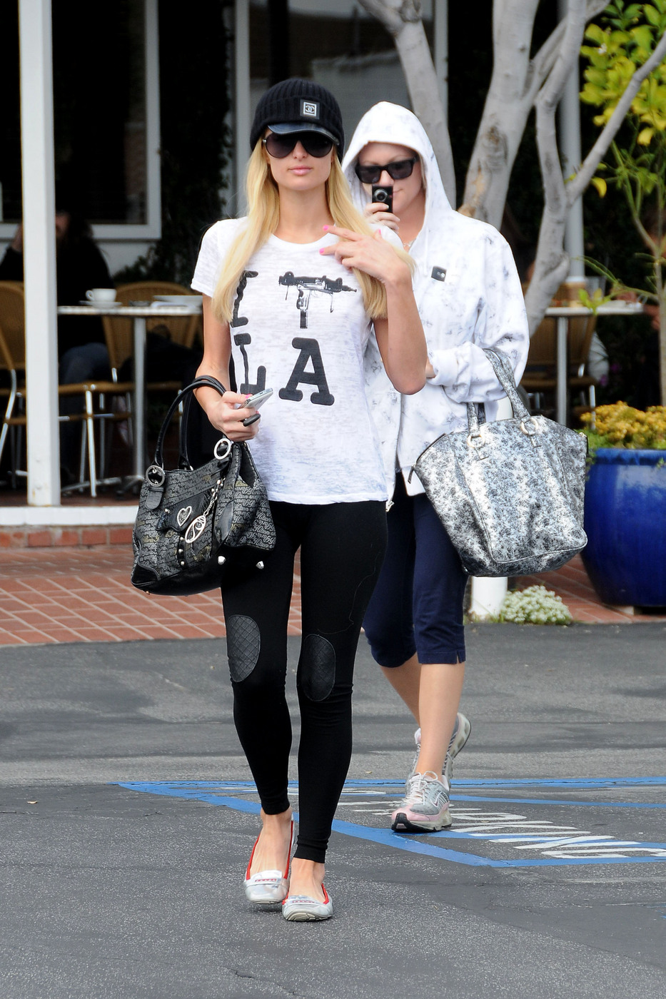 Paris Hilton heads back to her car after shopping at Fred Segal, with her friend recording her on her Flip video camera